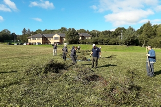 Trust volunteers and staff from Thomas Swan raking the meadow