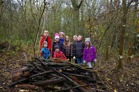 A group of children in front of a log pile