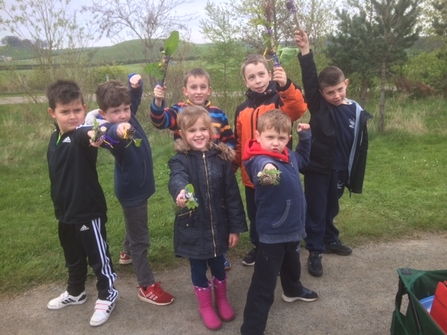 Children holding out their nature finds on a school visit with the Trust