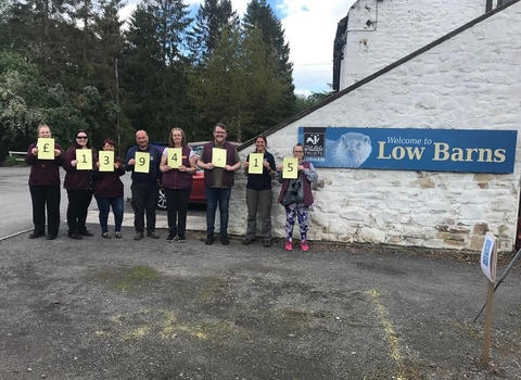 Team in front of Low Barns showing charity donation total